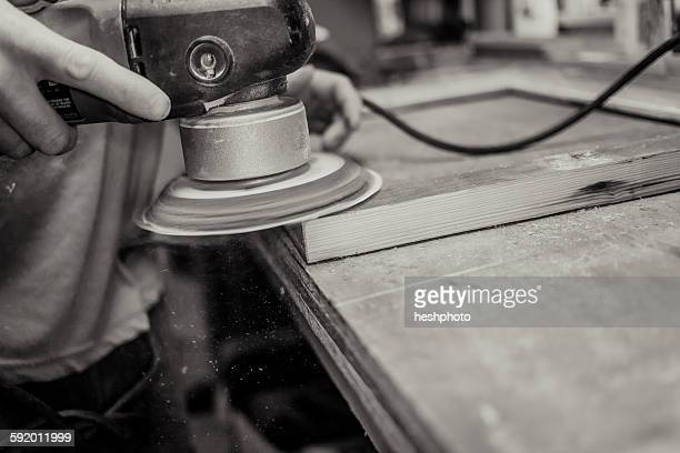 wood artist working in workshop, using machinery, close-up - heshphoto stock pictures, royalty-free photos & images