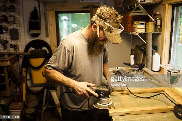 wood artist working in workshop, using machinery - heshphoto stock pictures, royalty-free photos & images