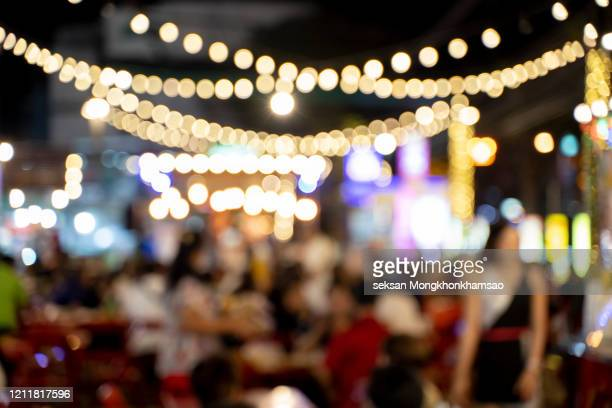 wood bar table with blur lighting in night street cafe - defocussed stock pictures, royalty-free photos & images