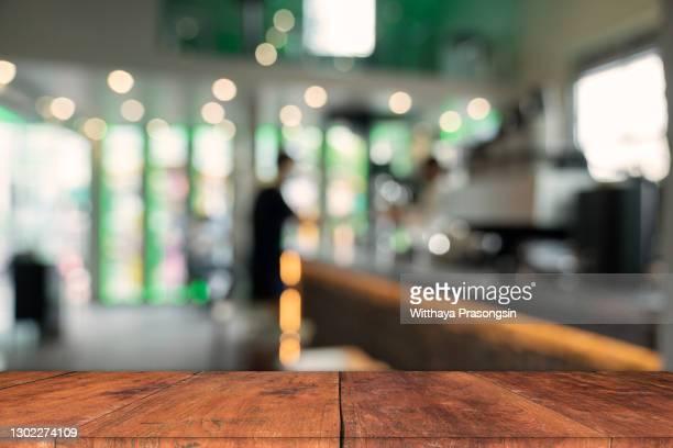 wood bar table with blur lighting in night street cafe - tischflächen aufnahme stock-fotos und bilder