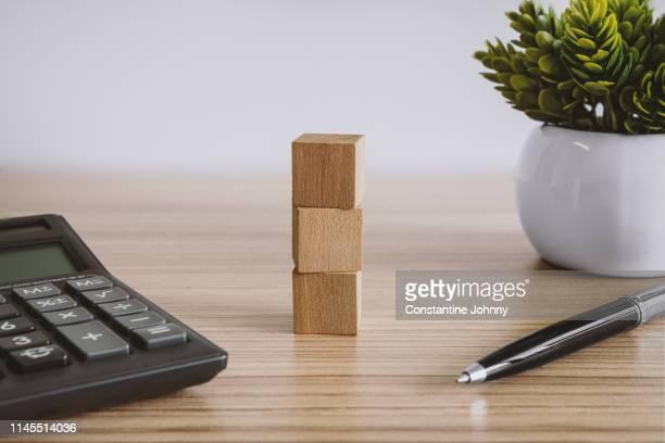 wood block, calculator and pen on wood desk - bureau ameublement photos et images de collection