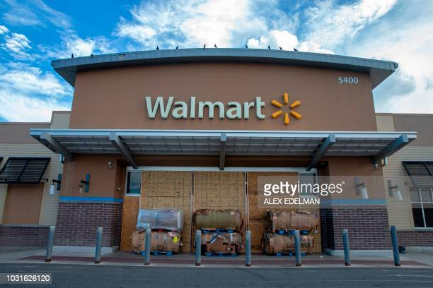 Wood boards and cardboard boxes block the entrance to a Walmart store in Kill Devil Hills in the Outer Banks of North Carolina on September 11, 2018....
