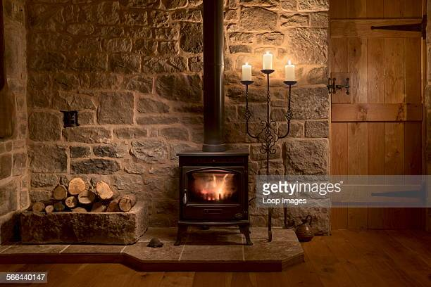 Wood burning stove and logs in a cottage living room.