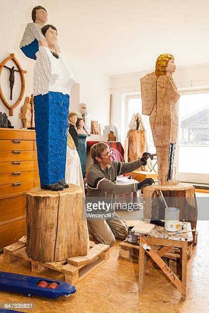 Wood carver in workshop painting his sculpture