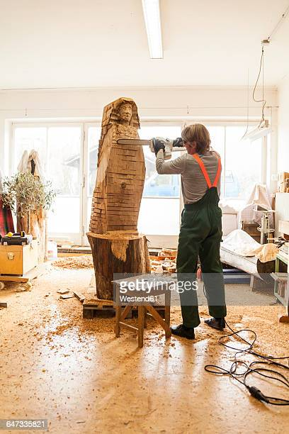 Wood carver in workshop working on sculpture with chainsaw