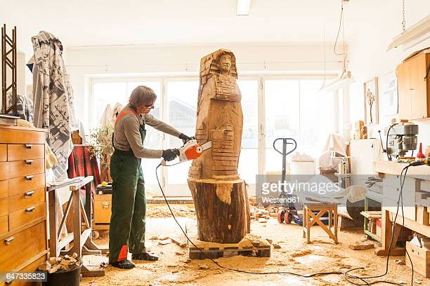 wood carver in workshop working on sculpture with chainsaw - sculpture stock pictures, royalty-free photos & images