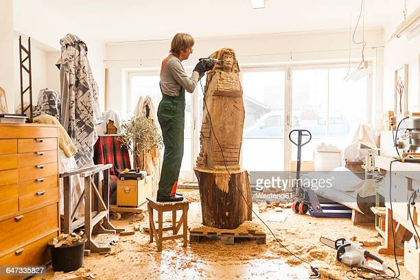Wood carver in workshop working on sculpture with milling machine, standing on stool
