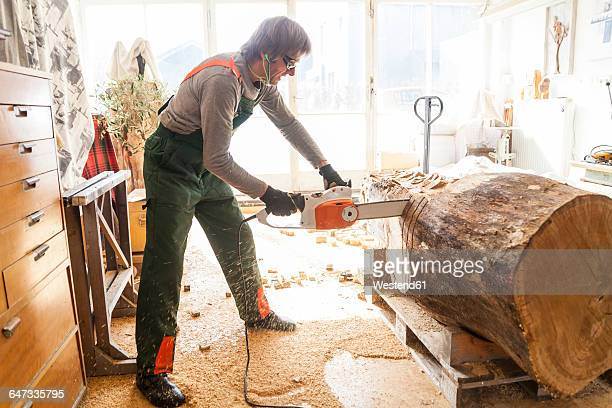 Wood carver in workshopworking on wood for a sculpture with a chainsaw