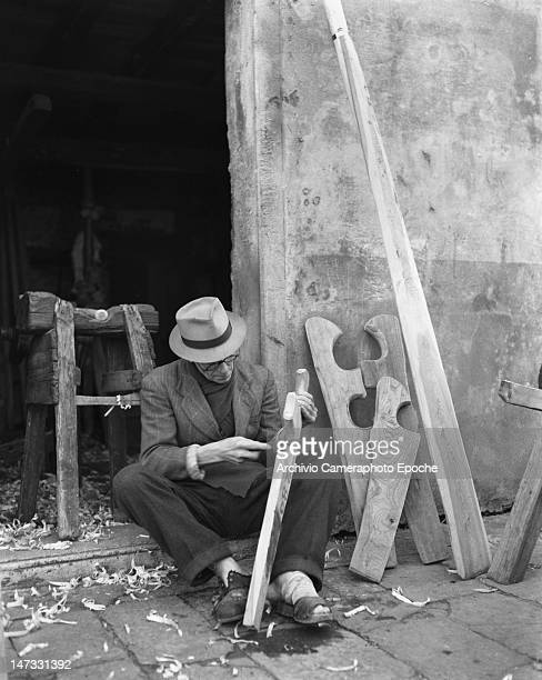 A wood carver sitting on the floor outside his workshop Chioggia Venice 1950