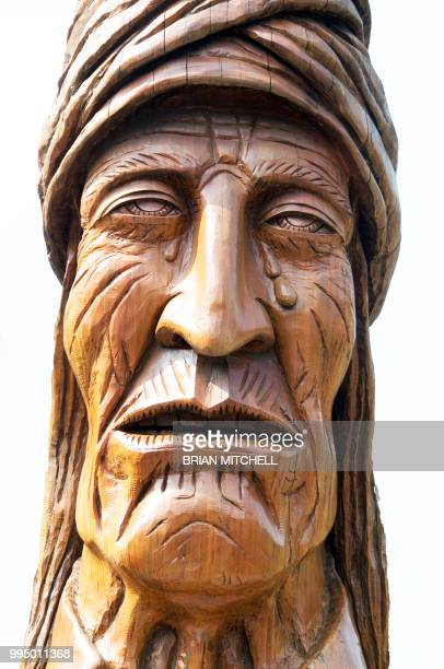 wood carving from a tree stump depicting a native american  cherokee indian crying tears. - cherokee culture stock pictures, royalty-free photos & images
