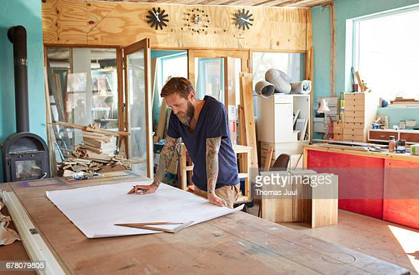 Wood Designer looking at blueprint in workshop