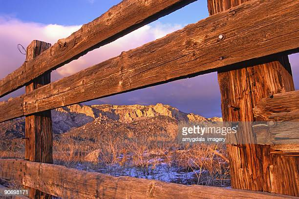 wood fence frames mountain sunset landscape - sandia mountains stock photos and pictures