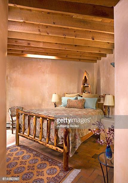 Wood framed bed in rustic country bedroom with timber framed roof and adobe walls Santa Fe New Mexico