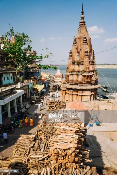 wood piles at manikarnika ghat - manikarnika ghat stock photos and pictures