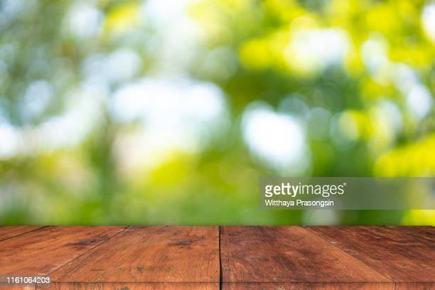 wood table top on blur abstract green from garden in the morning background.for montage product display or design key visual layout - tafel stockfoto's en -beelden