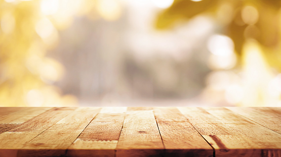 Wood table top on blur abstract natural foliage bokeh background, vintage tone 989111446