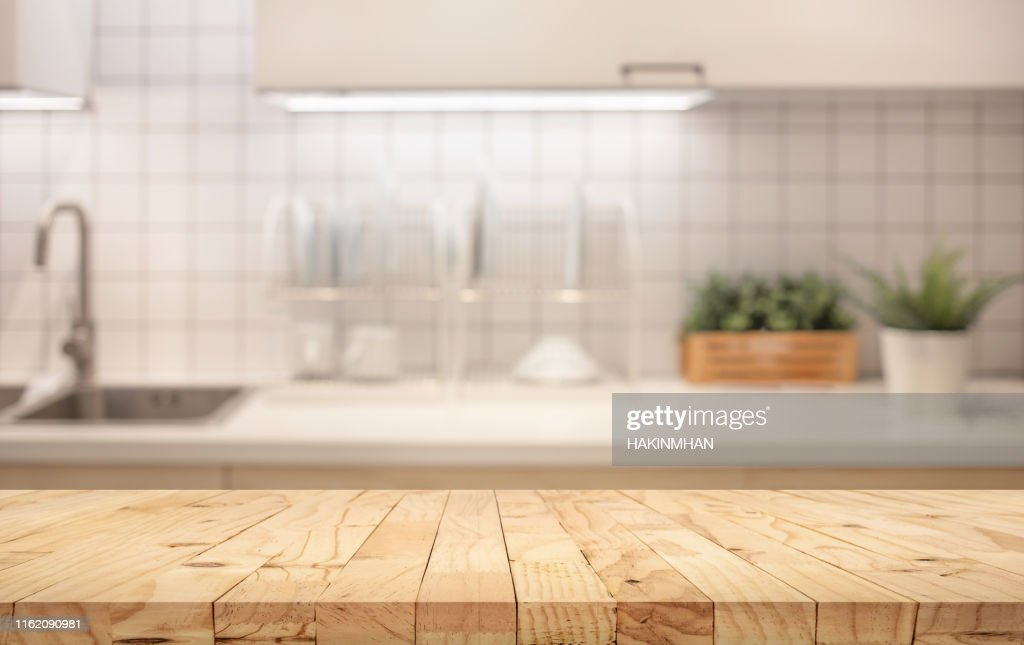 Wood table top on blur kitchen counter (room)background. : Stock Photo