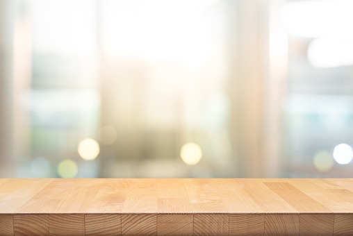 Wood table top on blur window glass,wall background 1129572627
