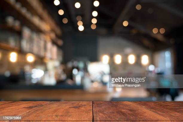 wood table top with blur of people in coffee shop or (cafe,restaurant )background - table stock pictures, royalty-free photos & images