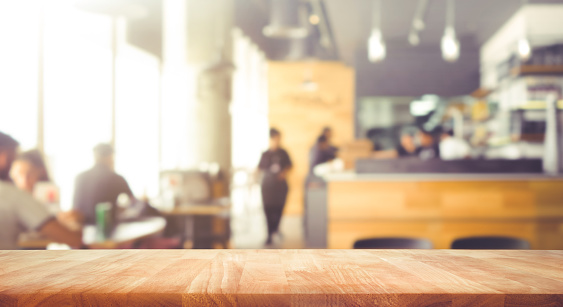 Wood table top with blur of people in coffee shop or (cafe,restaurant )background 967951076