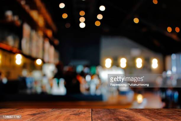 wood table with blur of people in cafe or restaurant on background. - brown stock pictures, royalty-free photos & images