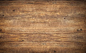 Wood texture background. Top view of vintage wooden table with cracks. Surface of old knotted wood with natural color, texture and pattern. Dark barn material.