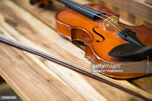 wood violin laid on wooden chair with bow