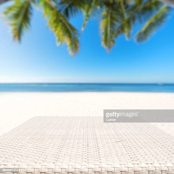 Wood weave table surface and tropical beach background