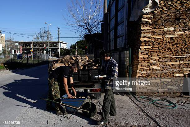 A wood yard worker loads firewood logs into a wheelbarrow for delivery to a customer in Athens Greece on Thursday Jan 9 2014 Prime Minister Antonis...