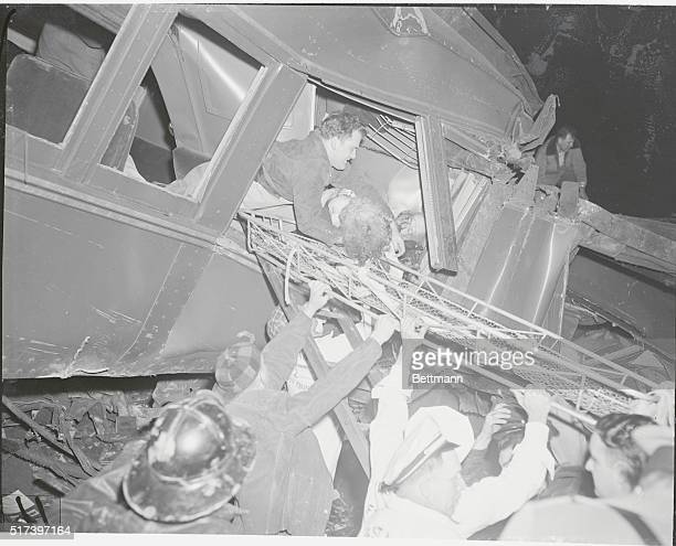 Woodbridge, New Jersey: Helping Hands. Ignoring the body of the dead man braced in the window, a rescue worker lifts an unconscious woman through the...