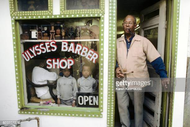 Woodcarver Standing in Front of Barber Shop