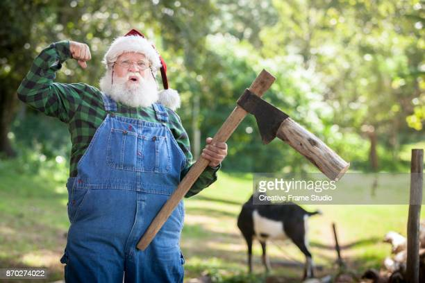 Woodcutter Santa Claus flexing arm muscle holding an ax while cutting wood on a meadow