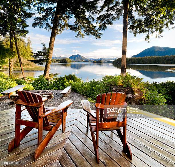 Wooden adirondack chairs on a deck overlooking the water, Tofino Chalet on Jensens Bay