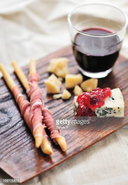 A wooden appetizer board with cheese, jelly and wine