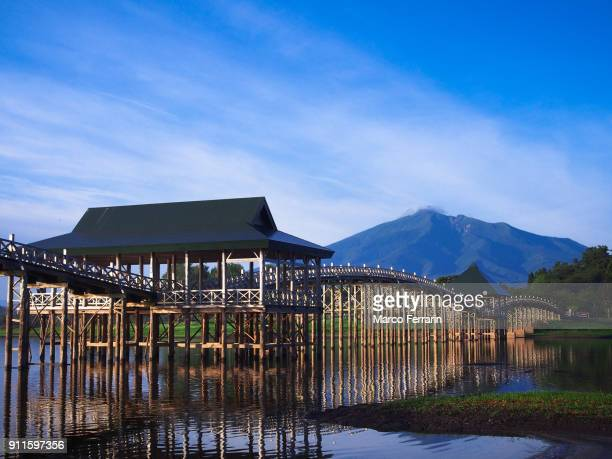 wooden arch bridge over lake with mountain and blue sky in the background - edo period ストックフォトと画像