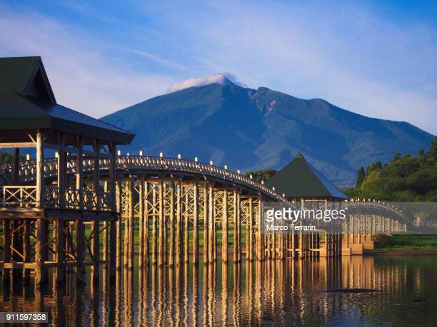 wooden arch bridge over lake with mountain and blue sky in the background - aomori prefecture stock pictures, royalty-free photos & images