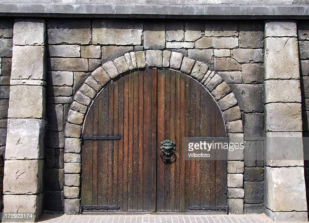wooden arched doors surrounded by stones in medieval design - castle stock pictures, royalty-free photos & images