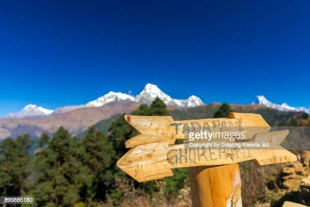 Wooden arrow shape direction sign during the trekking trail from Poon Hill to Tadapani.
