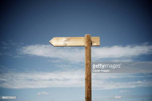wooden arrow sign against cloudy sky - pole stock pictures, royalty-free photos & images