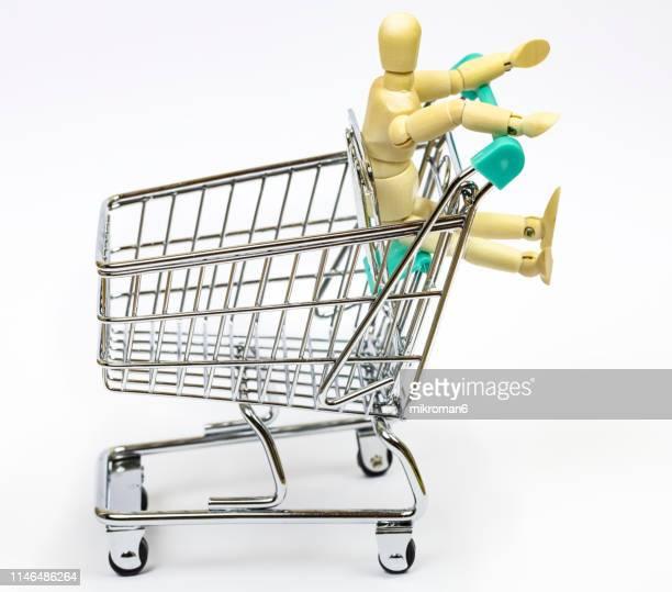 wooden artist mannequin sitting in empty shopping cart - mercado espaço de venda no varejo - fotografias e filmes do acervo