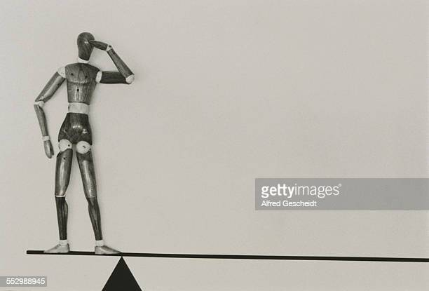A wooden artist's figurine standing on top of a seesaw 1993