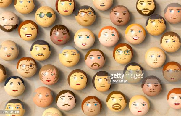 wooden balls with multi-ethnic faces on them. (top view) - multiculturalism stock pictures, royalty-free photos & images