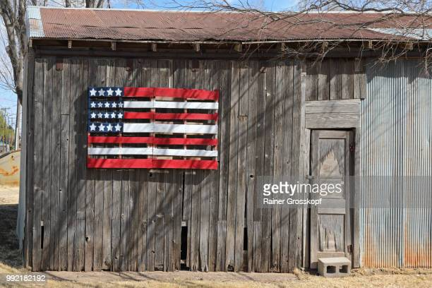 wooden barn with wooden american flag - rainer grosskopf stock-fotos und bilder