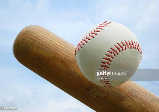 Wooden bat hitting a baseball with red stitching