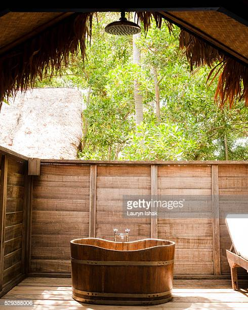 A wooden bathtub in an outdoor bathroom at Bon Ton Resort, Langkawi, Malaysia