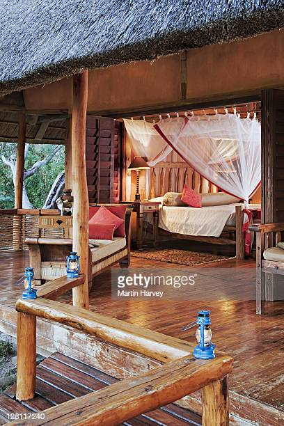 Wooden bed with decorative mosquito netting in villa. Exclusive luxury accommodation at Benguerra Lodge. Mozambique. (PR: Property released).