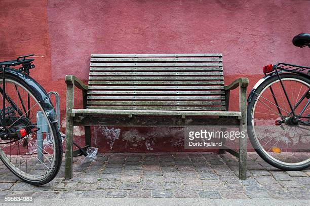 Wooden bench against red wall