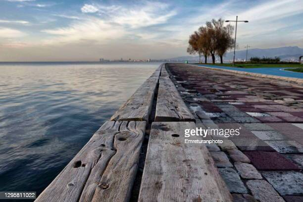 wooden bench along the waterfront,izmir bay - emreturanphoto stock pictures, royalty-free photos & images