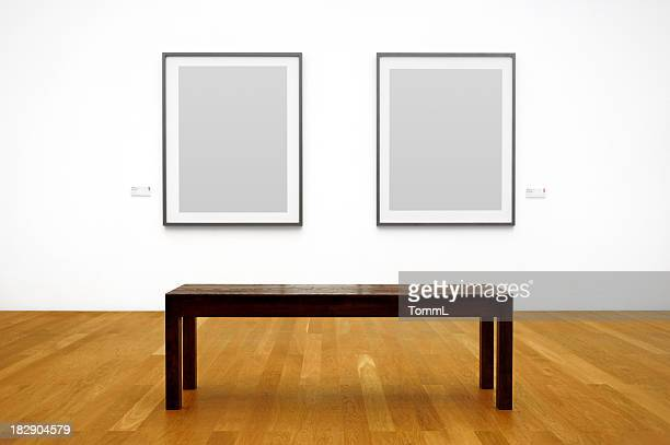 Wooden bench in front of picture frames hanging on a wall