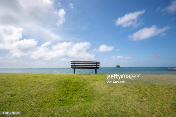 wooden bench in front of the sea - front view photos et images de collection